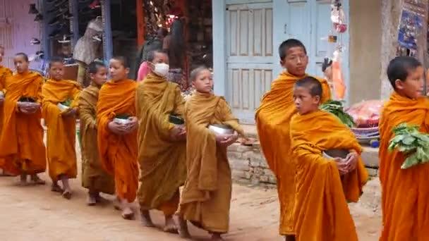 BHAKTAPUR, KATHMANDU, NEPAL - 18. Oktober 2018 Prozession junger buddhistischer Mönche, die um Almosen laufen, Kinder, die Spenden sammeln. Straßenalltag, orientalische antike Stadt nach dem Erdbeben.
