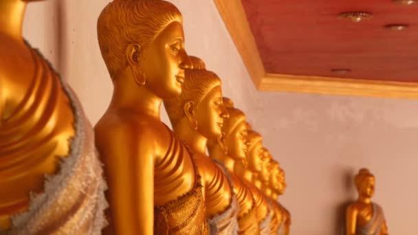Az adományokhoz való tálak a megvilágosodottak lábainál állnak. Fényesen sárga színű szobrok ülnek meditációs pozícióban. Azt jelenti, szobrok thai klasszikus hagyományos minták. Kilátás a nyilvános thai templomban