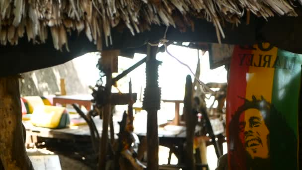 Relaxační jamajské konopí rasta marihuana reggae bar na tropické letní pláži z dřevěných větví a došků. Rastafarijské vlajky se žlutou, červenou a zelenou barvou a bob marley.