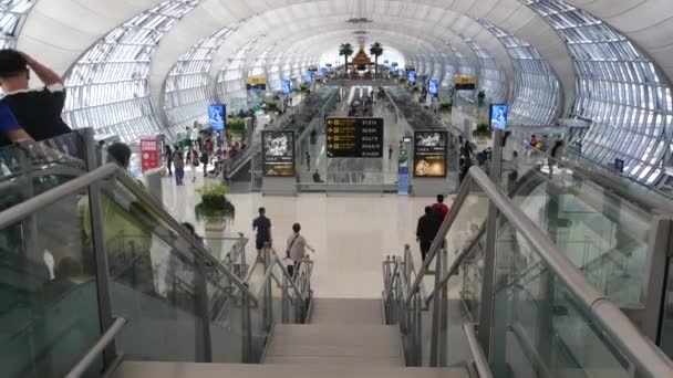 BANGKOK, THAILAND - 16. června 2019: Orientální stavba na letišti. Tradiční thajské konstrukce namontované na skleněných plošinách uvnitř přeplněného terminálu, Suvarnabhumi Airport people whaiting for boarding.