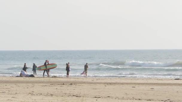 Oceanside, California USA - 8 Feb 2020: People walking on ocean beach, waterfront vacations resort. Surfer men with surfboard going surfing in sea waves.