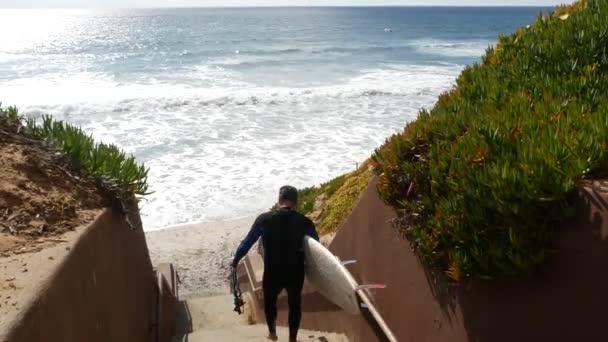 Karlovy Vary, Kalifornie USA - 29. února 2020: Surfaři se surfaři na schodech. Muž a žena jdou surfovat, pobřežní schodiště, přístup na pláž. Lidé za slunečného dne. Mladý pár a zdravý sportovní koníček.