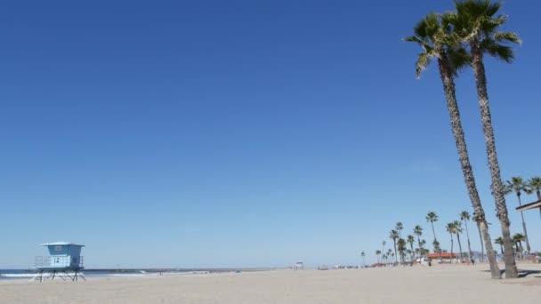 Palmy na bílé písečné pláži, oceánské pobřeží v Kalifornii USA. Záchranná věž, chata na strážní věži.