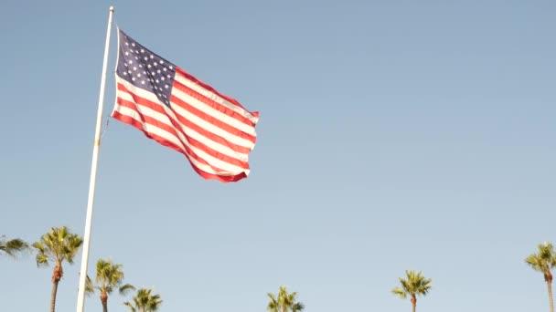 Palmy a americká vlajka, Los Angeles, Kalifornie USA. Léto estetiky Santa Monica a Venice Beach. Hvězdami posetý prapor, hvězdy a pruhy. Atmosféra vlastenectví v Hollywoodu. Stará sláva