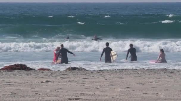 San Diego, Kalifornie USA - 19. listopadu 2020: Surfaři v oceánských vlnách se surfy, lidé surfující na pláži Mission. Rekreační sport, zdravý životní styl na pobřeží Pacifiku. Muži a ženy ve vodě