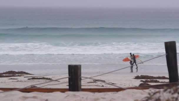 Monterey, California USA - 13 Dec 2020: Surfers with surfboards, sandy ocean beach. People surfing, misty coast in haze. Foggy rainy grey autumn or winter weather. Big huge surf waves, cold sea water.