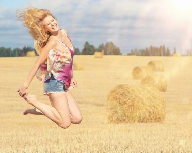 Blonde woman jumps in field