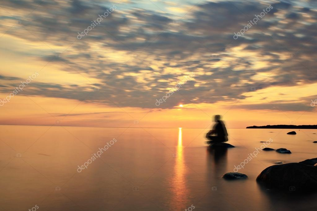 Man on the lake on sunset
