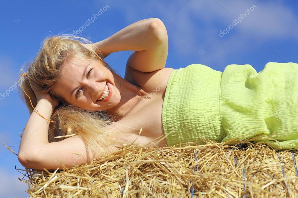 Blond woman lying on the hay