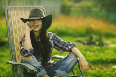 girl in a wide hat resting on a sun