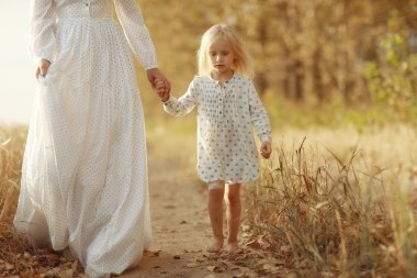 girl is with her mother in the autumn field