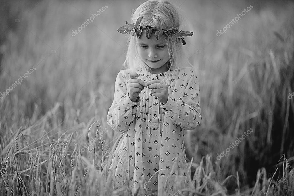 blonde little girl in the field with spikelets