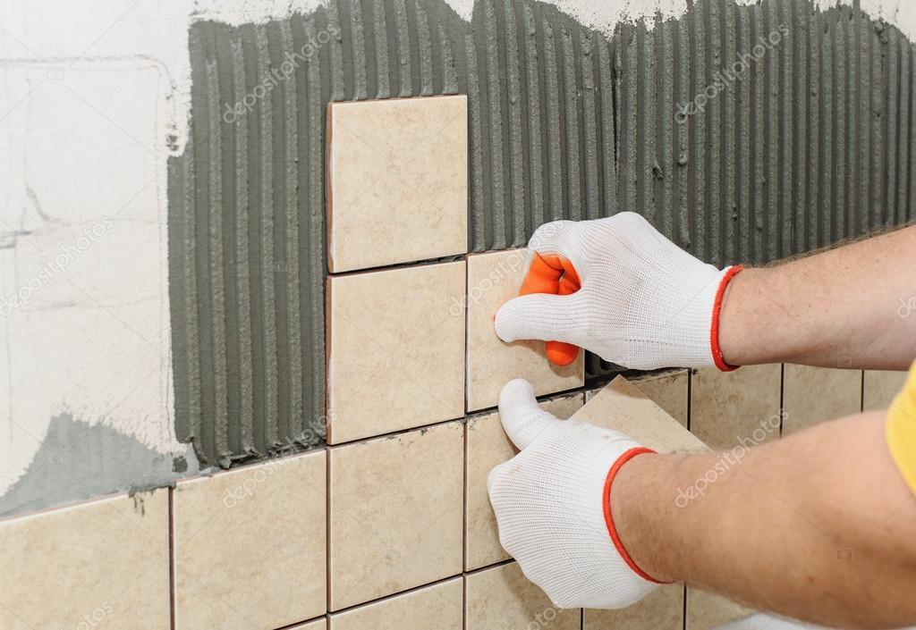 Lavoratore mettendo le piastrelle sul muro in cucina — Foto Stock ...