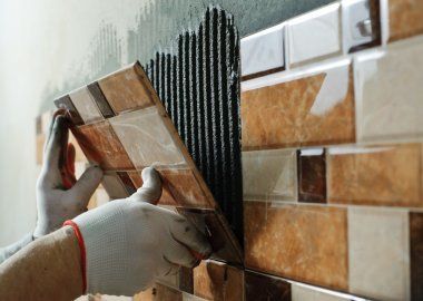 Laying Ceramic Tiles. Tiler placing ceramic wall tile in position over adhesive stock vector