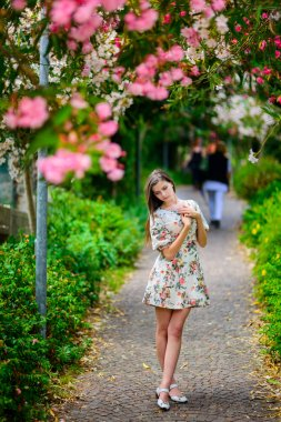 young girl standing near tree with flowers