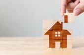 Immobilieninvestitionen und Haus Hypothek Finanzimmobilienkonzept. Hölzerne Würfelblock Puzzle mit Home-Bild