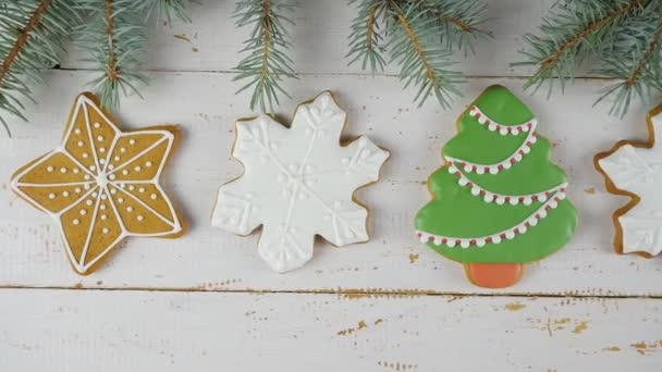 Mézeskalács dekoráció karácsonyra. Mézeskalács sütik fehér fából készült háttérrel. A mézeskalács sütik sorban vannak. Kilátás fentről. 4k-ben lőtték le.
