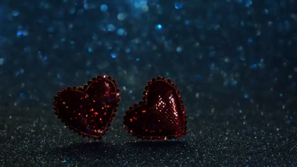 Bokeh of sparkling lights. Magic romantic abstract background. Two red hearts. The lights are shining. 4K