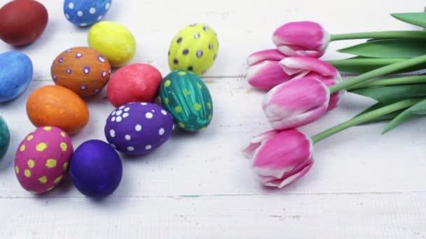 Velikonoce. Mnohobarevná velikonoční vajíčka a růžové tulipány