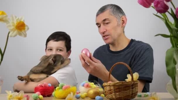 Családi játék egy húsvéti nyuszival. Apa és fia húsvéti nyuszifülekkel. A fiúnál van egy kutya. Csivava. 4K