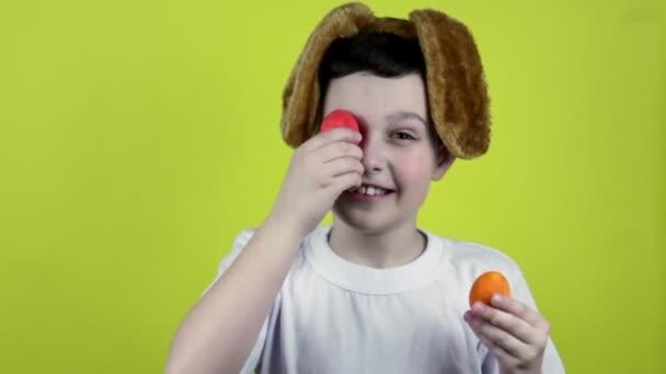 Frohe Ostern. Netter Junge bemalt Ostereier. Glücklicher kleiner Junge mit Eiern in den Händen. Hasenohren. Der Junge lacht
