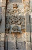 Lakkundi, Karnataka, India - 2013. november 6.: Brahma Jinalaya templom. Szürke és barna kőből készült közeli szobor külső falon.