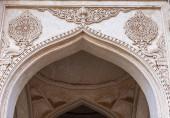 Vijayapura, Karnataka, India - 2013. november 8.: Fehér kőboltív közelsége az Ibrahim Rauza mecset homlokzatán látható, nem figuratív szobrokkal.
