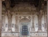 Vijayapura, Karnataka, India - 2013. november 8.: Bejárat az Ibrahim Rauza mauzóleumba, intenzíven díszített fallal, boltívekkel és oszlopokkal az ajtó körül. Főleg bézs-barna színekben. Nem figuratív szobrok.