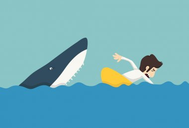 Businessman swimming to escape sharks
