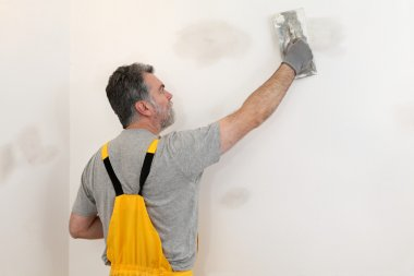 Worker repairing plaster at wall