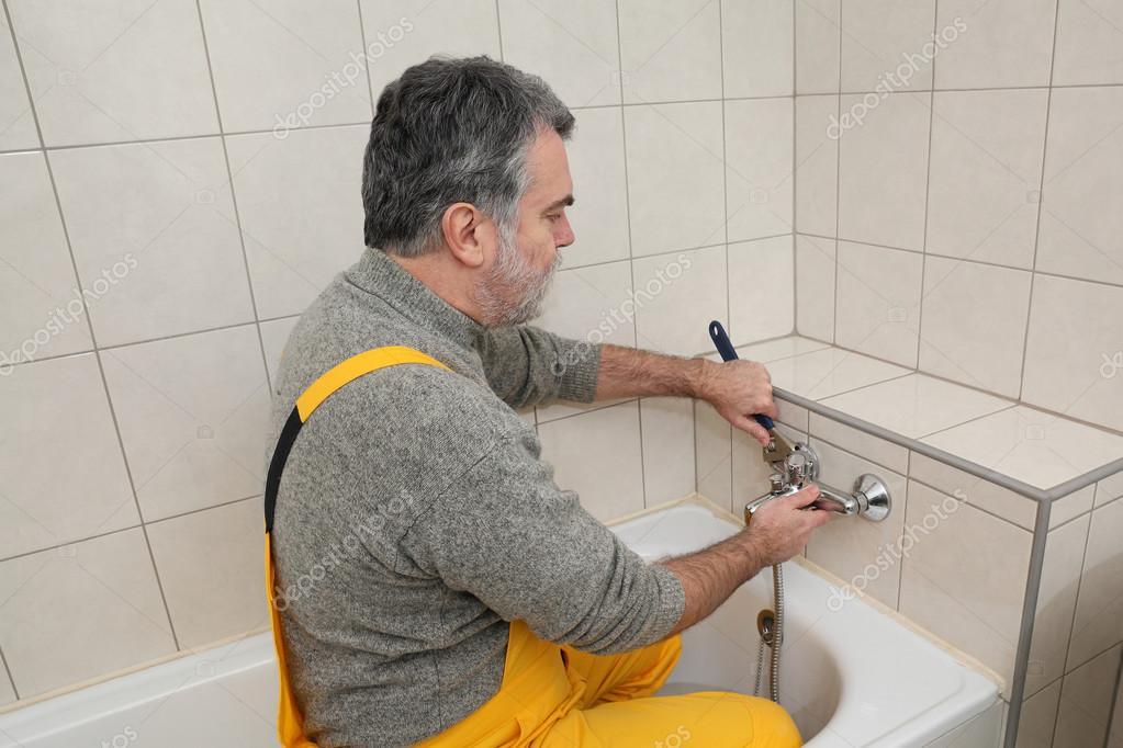Loodgieter werkt in een badkamer bad toob kraan vaststelling ...