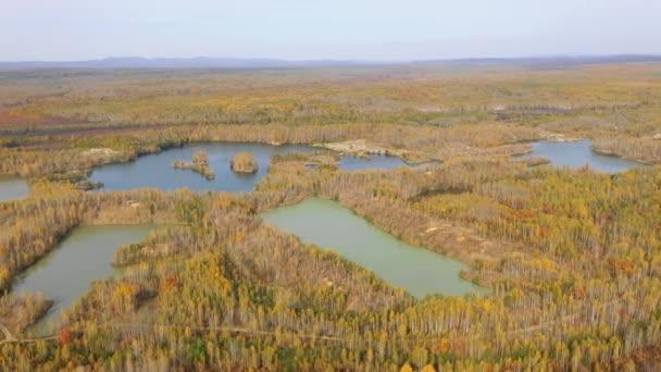 Kamera letí nad malebným jedovatým jezerem obklopeným podzimním lesem. Skládka po těžbě zlata
