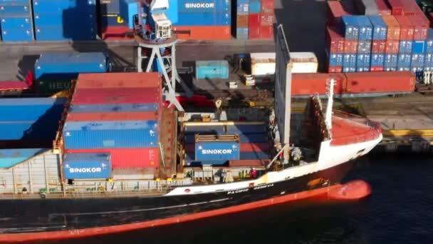 Vladivostok, Rusko - léto 2020 - Nákladní jeřáb nakládá na obchodní loď velký kontejner. Detailní záběr. Území kontejnerového terminálu Vladivostok. Pohled shora.