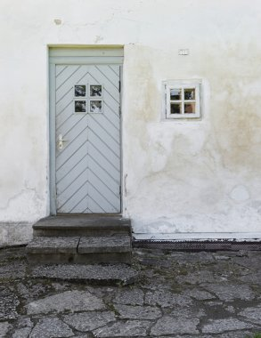 The old white plastered wall with a small window and a door and