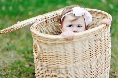 Little girl hiding in a basket