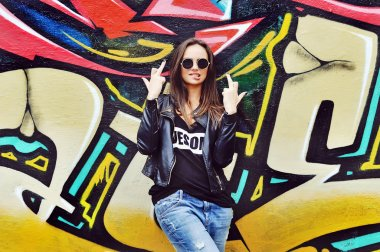 Stylish fashionable girl showing fuck off middle finger gesture