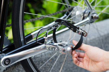 Hand with bicycle pedal detail