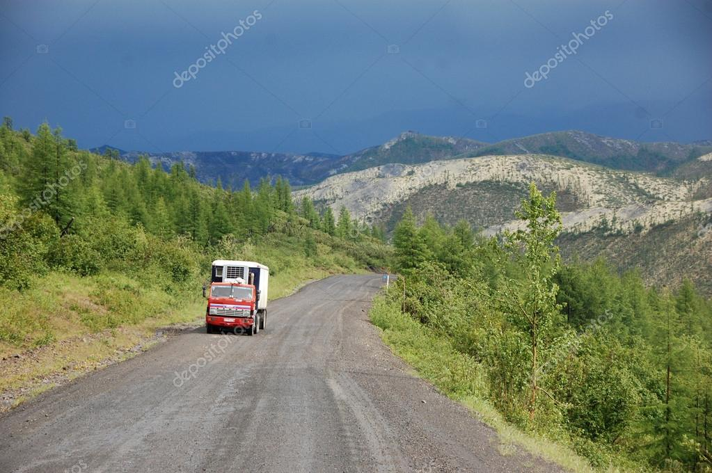 Truck at mountain gravel road Kolyma highway at Russian outback