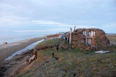 Abandoned broken mud hut at arctic island summer calm sea coast