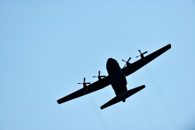 silhouette of hercules transport plane against the blue sky