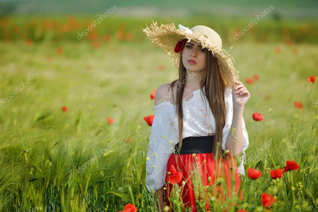 young beautiful woman on cereal field with poppies in summer