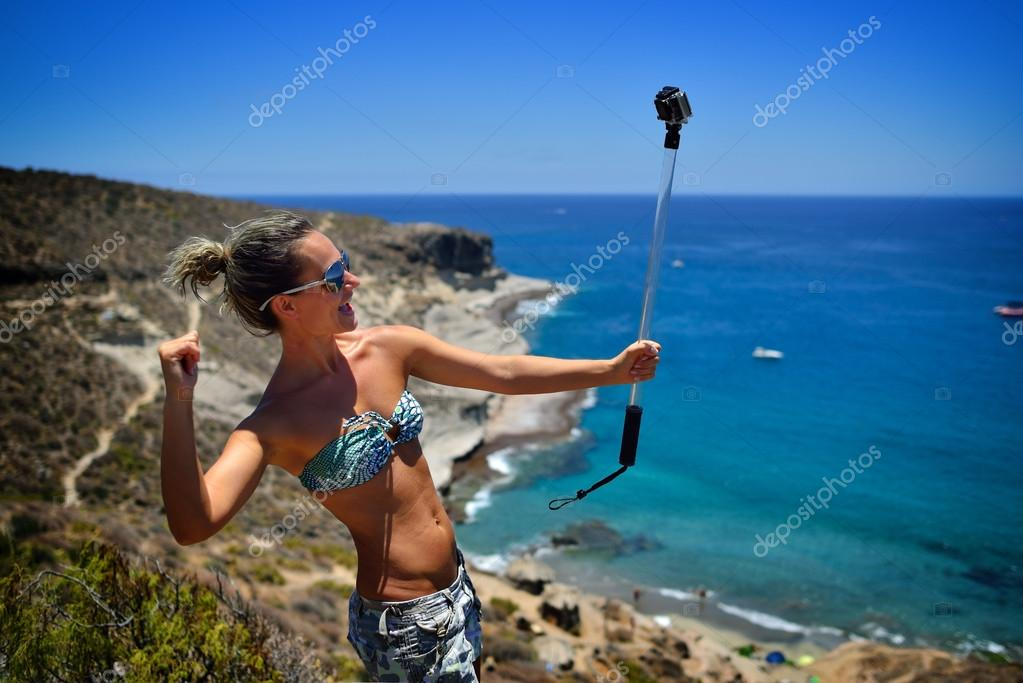 young woman on the beach in summer using gopro