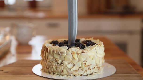 A közelkép óvatosan vágja fel a tortát egy késsel szeletekre. Eszterházy torta mandulával és bogyóval.