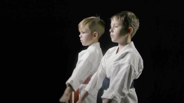 A karatégi fiúk gyakorolják az ütést a fekete háttéren