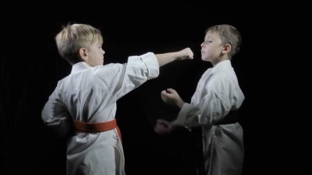 A karatégiákban a fiúk ütéseket és blokkokat készítenek fekete háttéren.