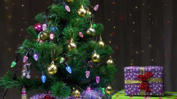 Zelený vánoční stromek a krásné dárky na pozadí blikající girlandy
