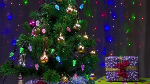 Krásné dárky a vánoční stromek na pozadí blikající věnce