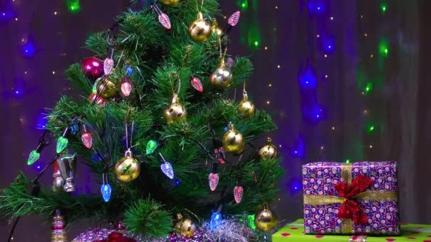Krásné dárky a zelený vánoční stromek na pozadí blikající věnce