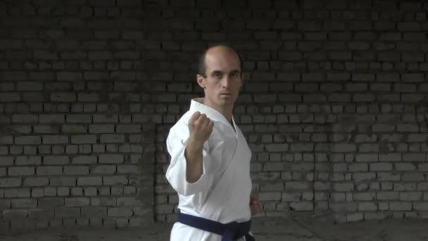 A téglafal hátterében egy felnőtt sportoló ütéseket és blokkokat készít a kezével.
