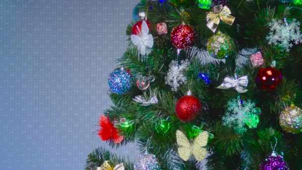 On a light gray background, a green Christmas tree decorated with colorful butterflies and toys